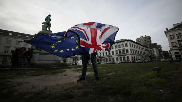A man unfurls a Union and EU flag outside the European