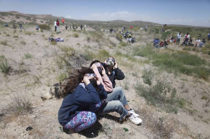 India Tv - People wear special glasses to watch a total solar eclipse in Piedra del Aguila, Argentina, Monday, Dec. 14, 2020. The total solar eclipse was visible from the northern Patagonia region of Argentina and from Araucania in Chile.