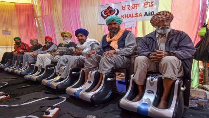 Farmers take foot massage, set up by an international NGO,