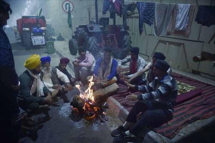 New Delhi: Farmers sit near a bonfire during their sit-in