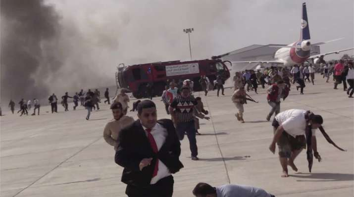 People run following an explosion at the airport in Aden, Yemen, shortly after a plane carrying the
