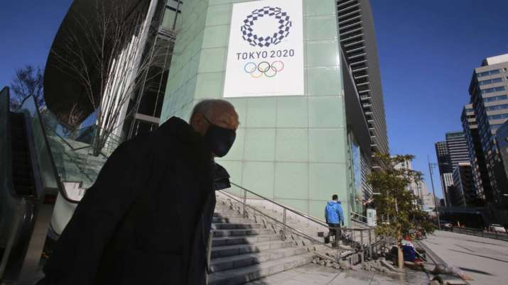 A man walks by the logo of Tokyo Olympic Games planned to