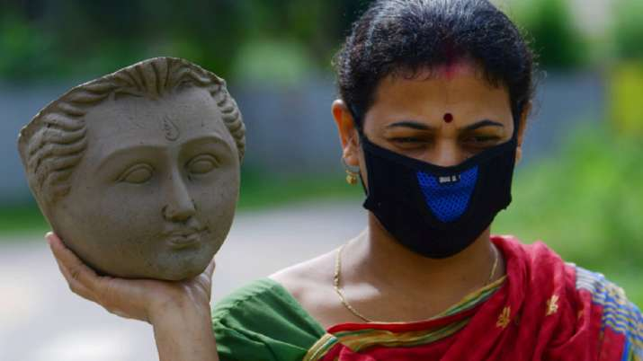 A woman artisan carries the face-idol of Goddess Durga at a studio in Agartala.
