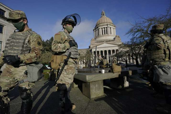 Members of the Washington National Guard stand at a sundial near the Legislative Building