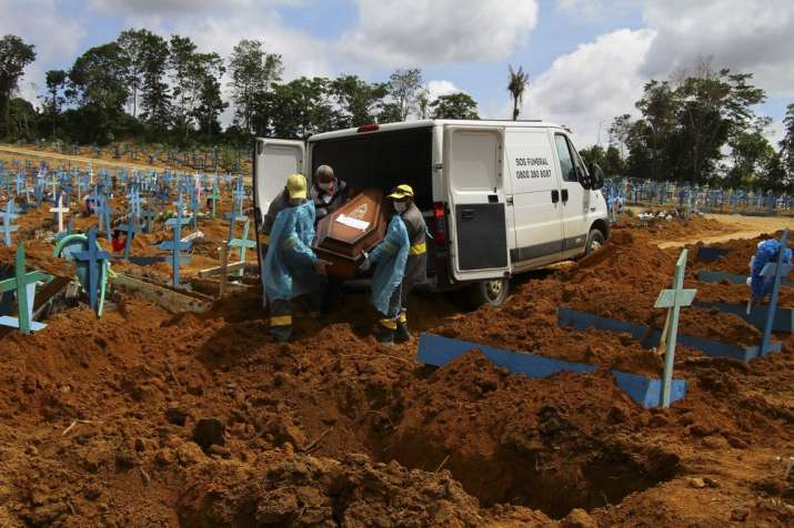 Cemetery workers carry the remains of 89-year-old Abilio Ribeiro, who died of the coronavirus, to bu