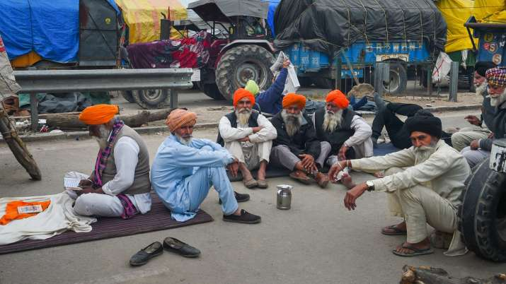 Farmers take rest during their ongoing protest against the new farm laws, at Singhu border in New De