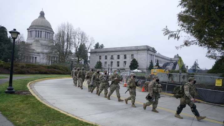 Washington National Guard members walk in formation away from the Legislative Building.