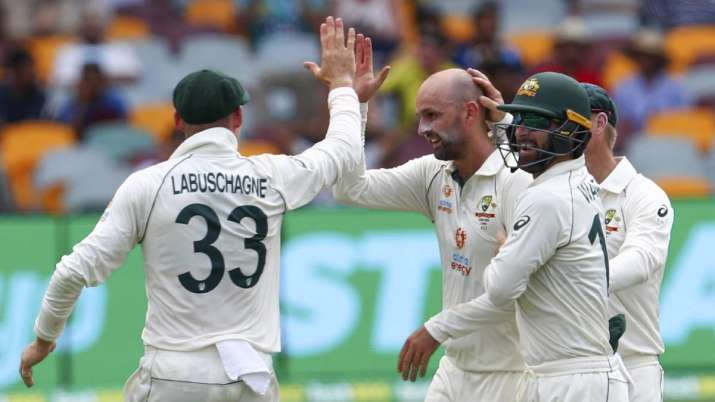 India Tv - Australia's Nathan Lyon, left, is congratulated by teammate's Matthew Wade and Marnus Labuschagne, left, after taking the wicket of India's Rohit Sharma during play on day two of the fourth cricket test between India and Australia at the Gabba, Brisbane, Australia, Saturday, Jan. 16