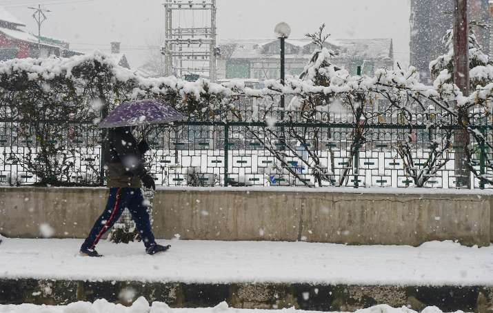 India Tv - Srinagar: A pedestrian holding an umbrella walks on a snow-covered pavement during snowfall in Srinagar, Sunday, Jan. 3, 2021.
