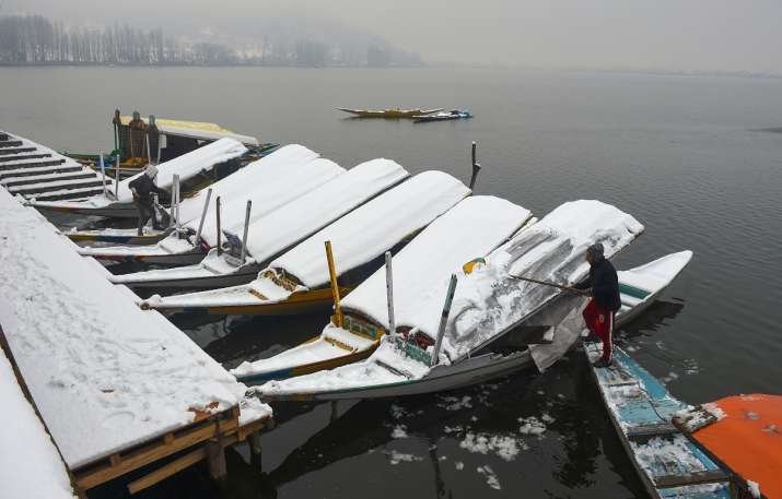 India Tv - Srinagar: A boatman clears snow from the roof of a Shikara after fresh snowfall at Dal Lake, in Srinagar, Sunday, Jan. 3, 2021.