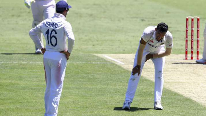India's Navdeep Saini, right, reacts after injuring his leg
