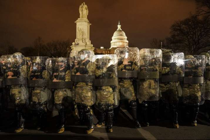 District of Columbia National Guard stand outside the Capitol after a day of rioting protesters.