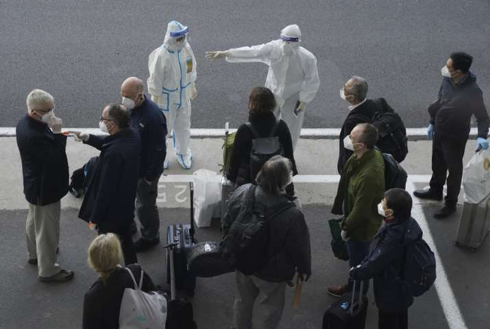 A worker in protective coverings directs members of the World Health Organization (WHO) team on thei