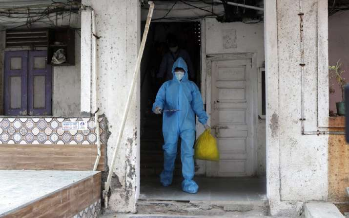 A health worker comes out of a residential building during a door to door screening for COVID-19 peo