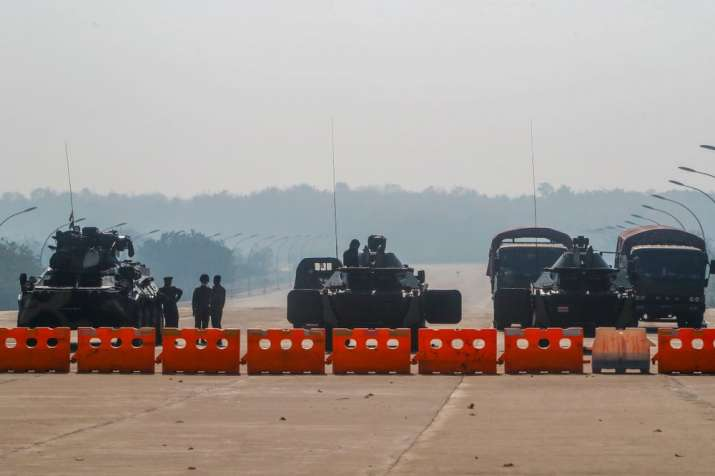 Myanmar's military stand guard at a checkpoint manned with an armored vehicles blocking a road leadi