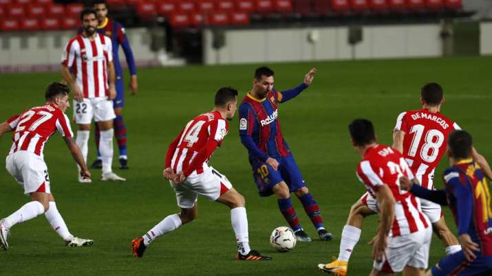 Barcelona's Lionel Messi, center, plays the ball during the