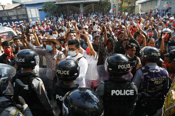 Residents and protesters face riot police as they question them about recent arrests made in Mandala