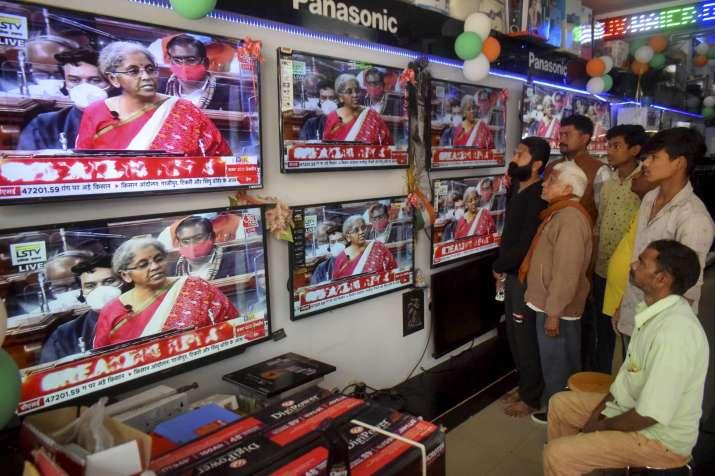 India Tv - People watch Finance Minister Nirmala Sitharaman presenting Union Budget 2021-21 on television sets, at an electronics store in Prayagraj, Monday, Feb. 01, 2021.