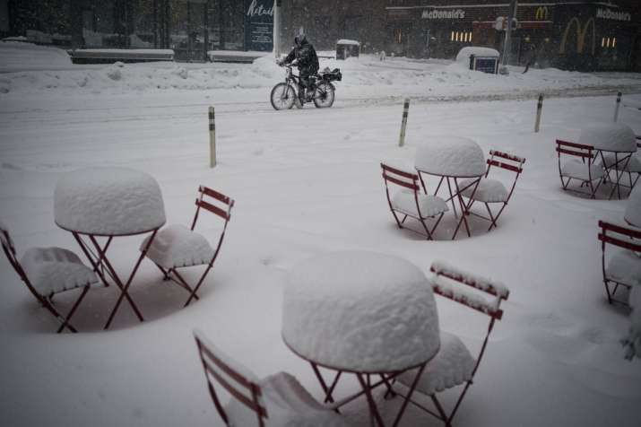 A man delivers food on his electric bicycle as he rides past snow-covered dining tables in midtown d