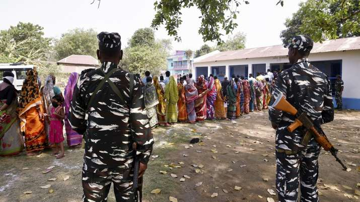 Paramilitary jawans guard as people wait in a queue to cast