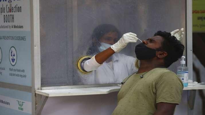 A health worker takes a nasal swab sample at a COVID-19