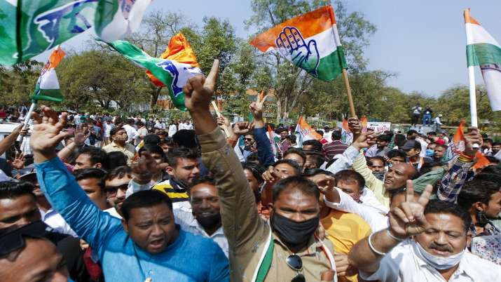 Congress party workers and supporters gather outside the
