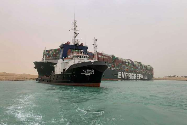 Suez Canal Authority, a boat navigates in front of a cargo ship, Ever Given, Wednesday, March 24, 20