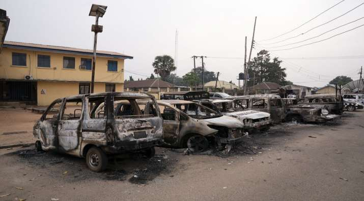 Burned vehicles are parked outside the police command