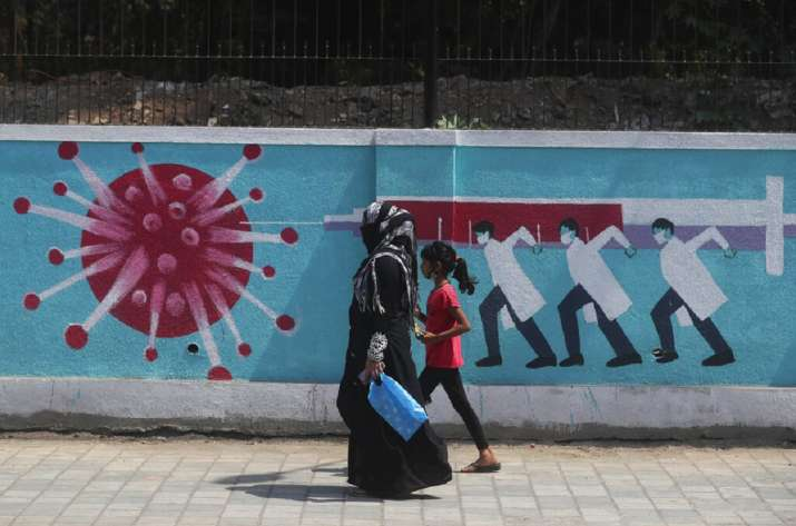 A woman along with a girl walk past a graffiti, depicting