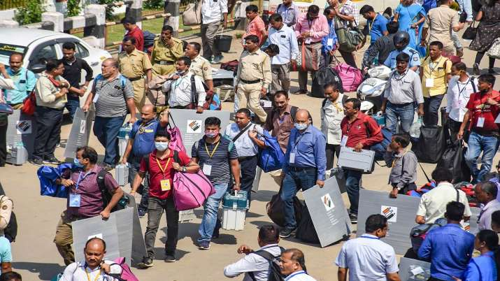 Polling officials carry Electronic Voting Machines (EVMs)