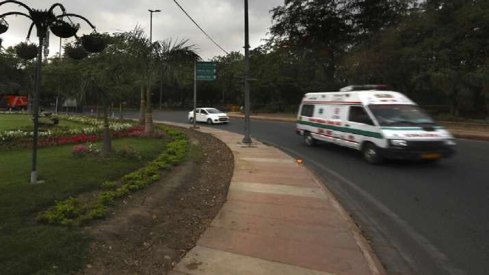 An ambulance carrying a patient drives past a Coronavirus