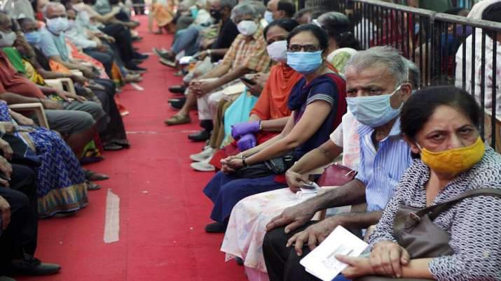 People wait to receive COVID-19 vaccine in Mumbai.