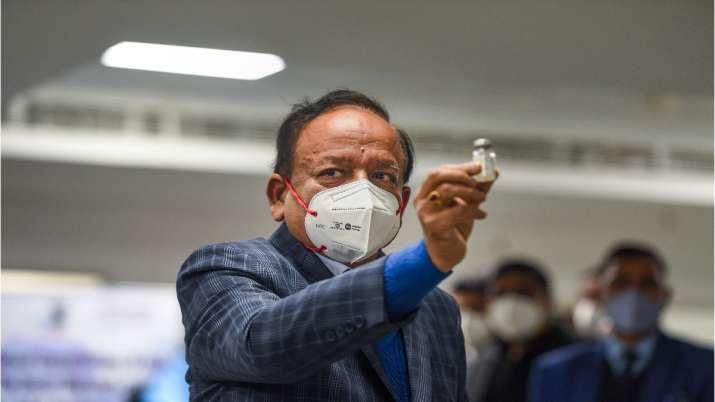 Union Health Minister Harsh Vardhan displays a Covishield