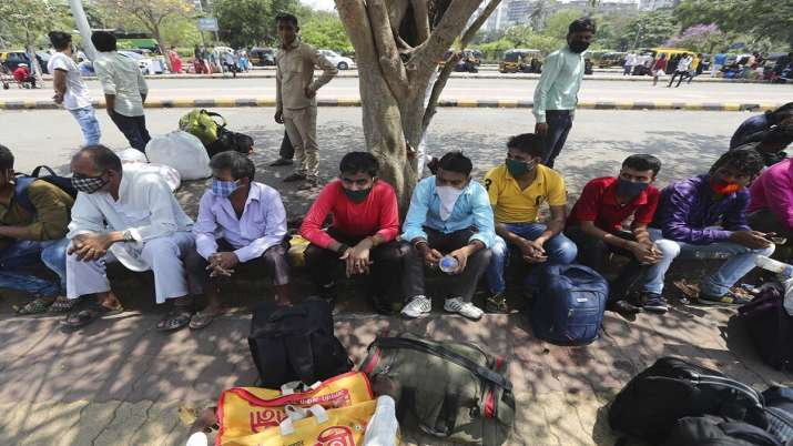 Migrant workers from Bihar state wearing face masks wait