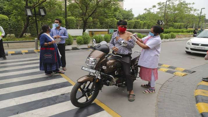 A man on a motorcycle gets inoculated against COVID-19