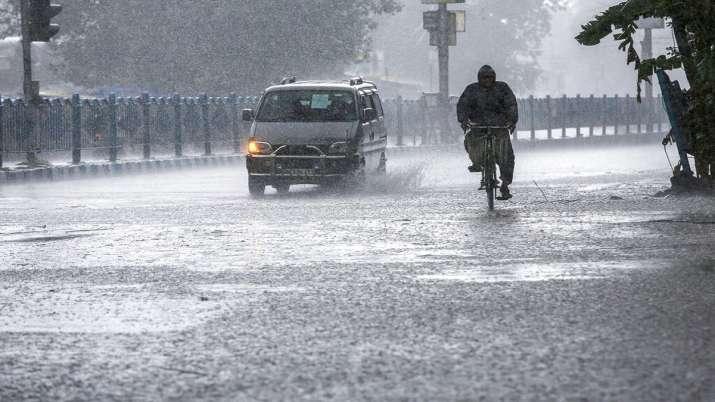A man pedals through heavy rain.
