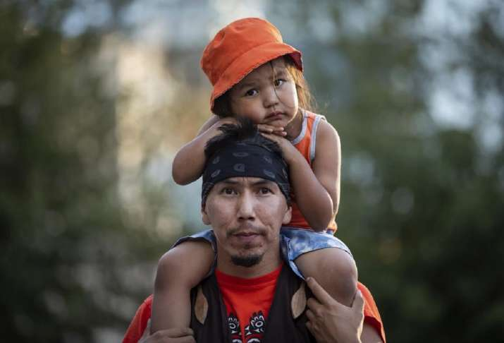 Cowichan Tribe member Benny George holds his child Bowie,