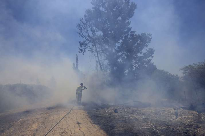An Israeli firefighter attempts to extinguish a fire caused