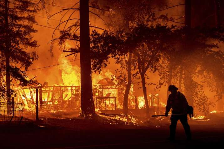 India Tv - A firefighter passes a burning home as the Dixie Fire flares in Plumas County, Calif., Saturday, July 24, 2021. The fire destroyed multiple residences as it tore through the Indian Falls community.