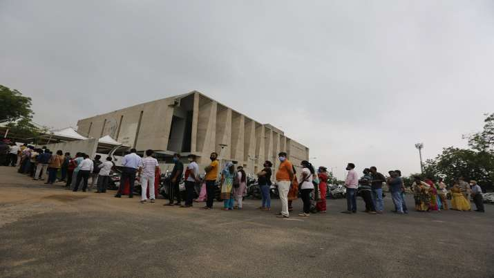 People stand in a queue to get vaccinated for COVID-19 at a