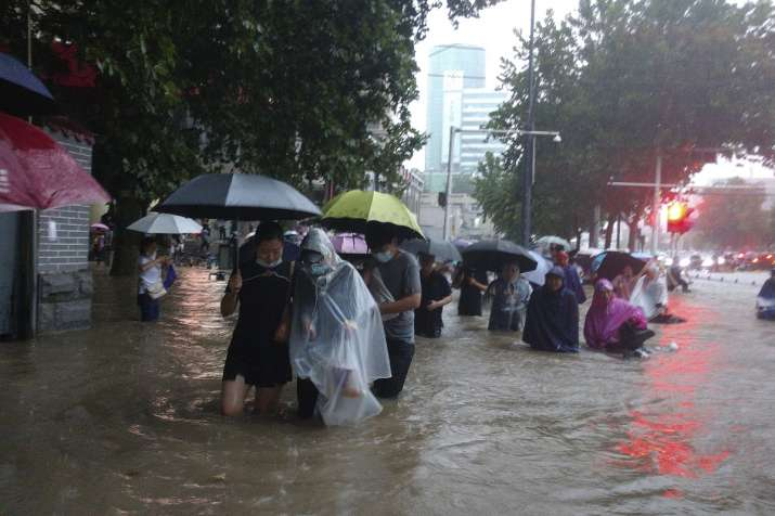 People move through flood water after a heavy downpour in