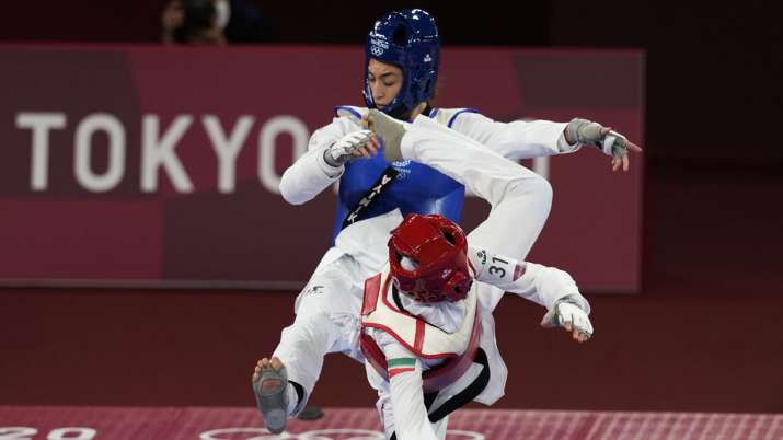 India Tv - Iran's Nahid Kiyani, front, attacks Kimia Alizadeh, of the Refugee Olympic Team, during the women's 57kg match at the 2020 Summer Olympics, Sunday, July 25