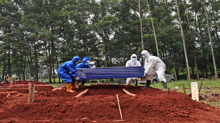Workers in protective suits prepare to lower a coffin