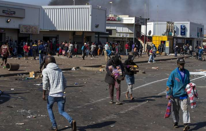 India Tv - People carrying groceries looted at Letsoho Shopping Centre in Katlehong, east of Johannesburg, South Africa.