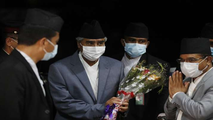 Sher Bahadur Deuba, center holding bouquet, arrives to