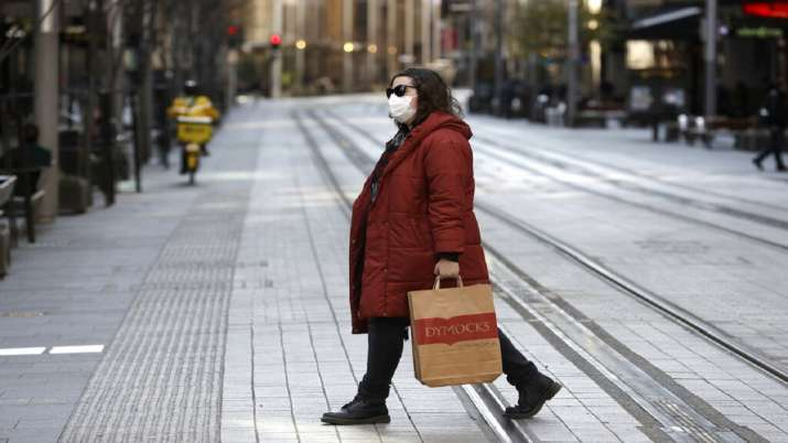 A woman crosses a normally busy street in Sydney,