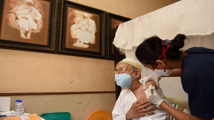 An elderly person receives a dose of Covid-19 vaccine, at a