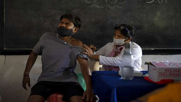 A man reacts as a health worker inoculates him against the