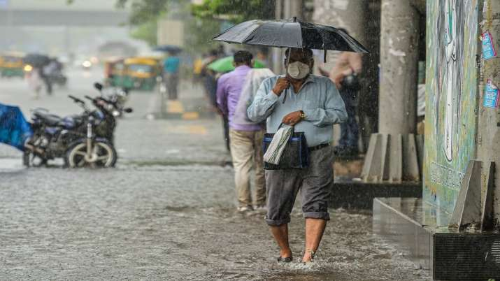 A man carries an umbrella as he walks on a waterlogged road