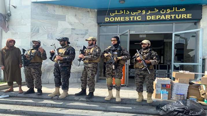 Taliban fighters stand guard inside the Hamid Karzai